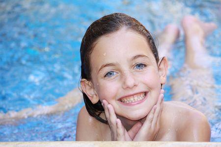 una niña acostada en una piscina con salpicaduras de agua sobre su rostro mirando a la cámara sonriendo