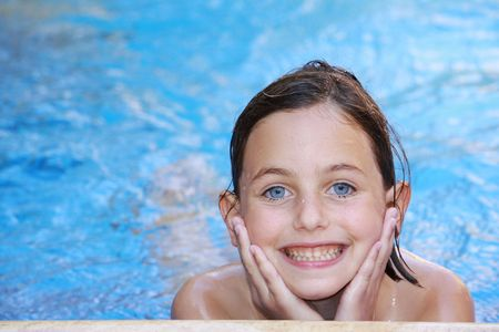 a pretty girl with blue eyes swimming in a swimming pool