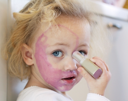 mischievous: a child painting her face with lipstick