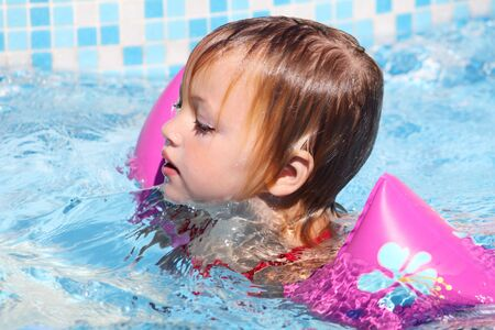 armbands: a child swimming for dry ground with armbands