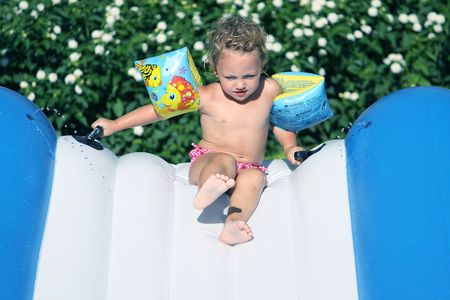 a toddler in armbands coming down a waterslide