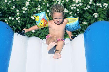 un niño en una brazaletes bajando Waterslide