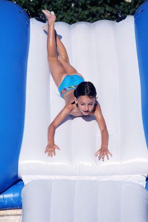 una niña va a desaparecer por un tobogán acuático en su barriga