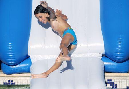bathing costume: a young girl having fun going down a water slide Stock Photo
