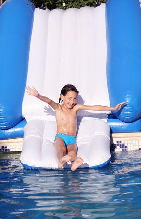 una joven chica bonita con ojos azules, deslizarse en un tobogán acuático en una piscina Foto de archivo