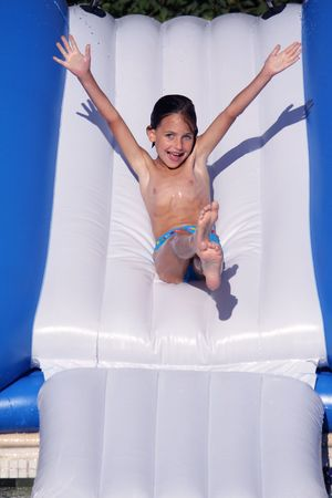 a girl going down a water slide with arms wide open in the air and a lovely happy expression