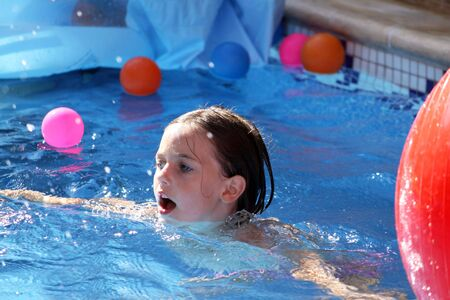 a pretty young girl swimming in a pool amongst colorful balls doing stroke photo
