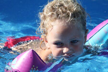 �ber Wasser: ein Kleinkind Schwimmen mit Schwimmfl�gel halten flott in einem Schwimmbad