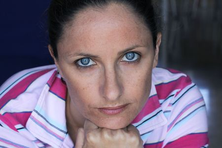a caucasian female natural portrait with blue eyes looking at the camera with her hand in a fist held under her chin