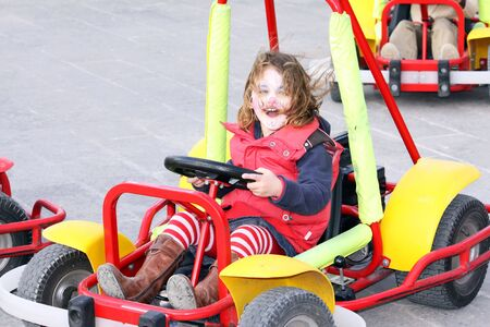a caucasian girl on a go-kart having lots of fun with her face painted