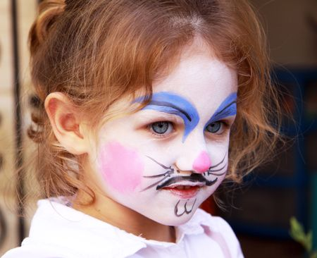 a caucasian little girl with her face painted as a rabbit looking away from the camera