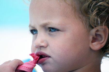 caucasian una niña mirando fuera de la cámara en morder algo con profundidad de campo