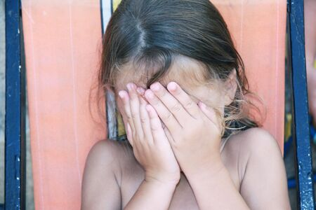 a caucasian young girl covering her face with her hands photo