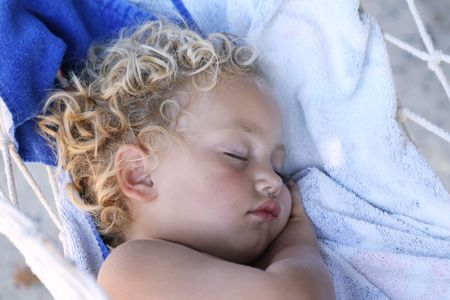 uno caucasica bambino profondamente addormentato su un amaca con la mano posta sotto uno guancia