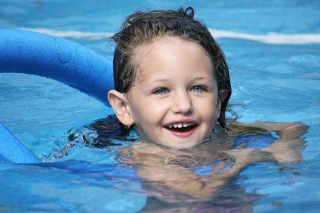 una piscina niña blanca en una piscina con un fideo
