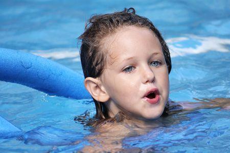 chica caucásicos nadando en una piscina con un fideo bajo sus brazos para mantenerla afloat