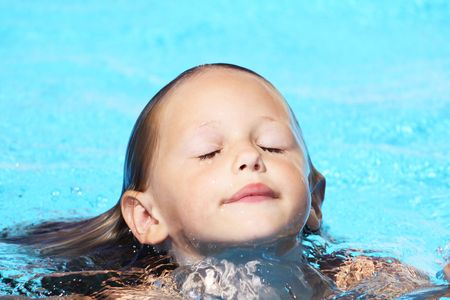 coming up with: a young caucasian girl emerging from the water with her eyes closed and water dripping off her face