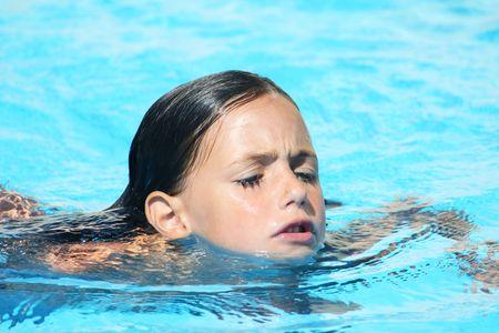un caucásico natación golpe niño de pecho con una mirada de concentración en su rostro en una piscina