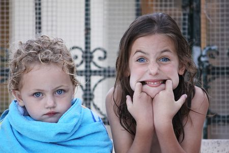 brat: two caucasian sisters, the youngest is looking serious wrapped up in a beach towel and the elder sister is pulling a funny face Stock Photo