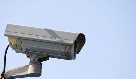 Cámara de seguridad de CCTV sobre un fondo de cielo azul mostrando signos de meteorización