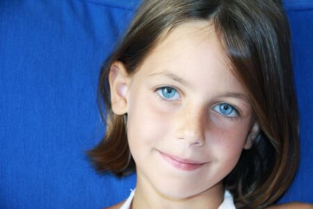 portrait of a pretty shy caucasian girl with blue eyes on a blue background Stock Photo - 5678001