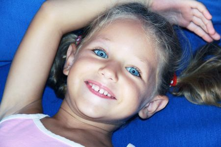 a happy caucasian child lying down with her arm above her head smiling on a blue background