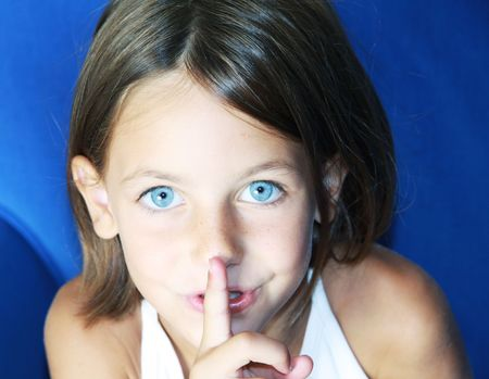 silent: a caucasian child with her forefinger to her mouth saying shhh to be quiet