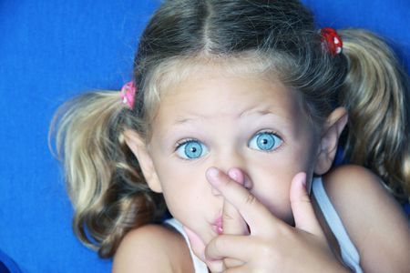 a young caucasian child with her hands to her mouth making a gesture to be quiet with a lovely expression on her face Stock Photo - 5678002