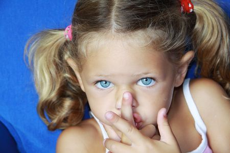 a young caucasian child with her hands to her mouth making a gesture to be quiet with a lovely expression on her face