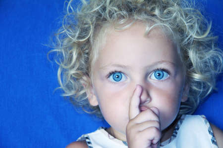 a young caucasian child with her hands to her mouth making a gesture to be quiet with a lovely expression on her face photo