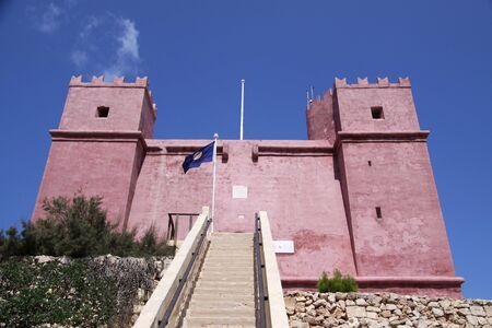 a red tower known as st.agathas tower situated in mellieha, in the maltese islands photo