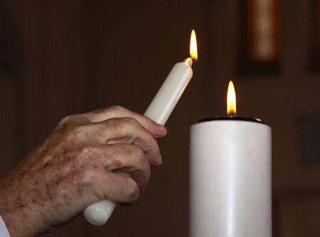 un sacerdote de una vela de iluminación como un símbolo de amor durante una ceremonia de bautismo
