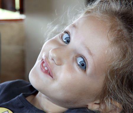 Retrato de niño encantador con ojos azules y una sonrisa sonsacadora
