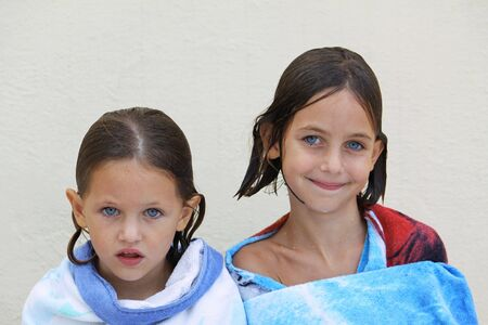 caucasian sisters with blue eyes wrapped in a beach towel just after having a swim photo
