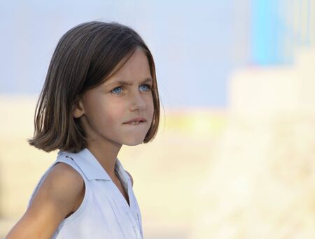 a caucasian young child with bob hair and blue eyes looking away from the camera biting her bottom lip photo