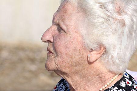 Ritratto di profilo di una donna anziana indoeuropea con capelli bianchi grigio