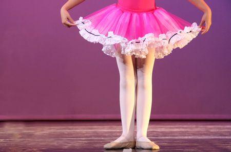 una joven bailarina en primera posición, ensayando en el escenario