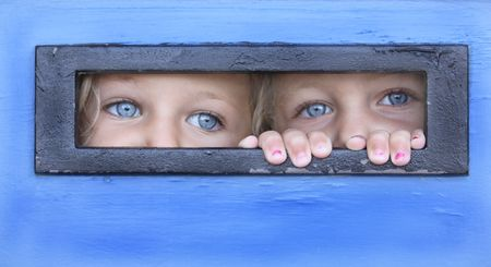 hermanas que se esconde detrás de una puerta que se espiándola a través de un cuadro de carta Foto de archivo