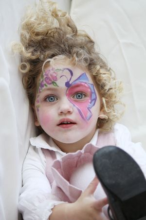 face paint: portrait of a young child with her face painted and foot in the air looking towards the camera
