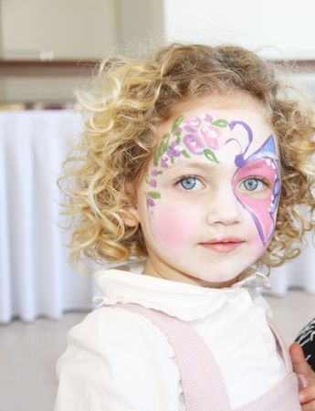 portrait of a caucasian child with her face painted with a butterfly