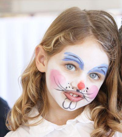 gezicht: portret van een vrij caucasian meisje met blauwe ogen met haar gezicht geschilderd als een konijn  Stockfoto