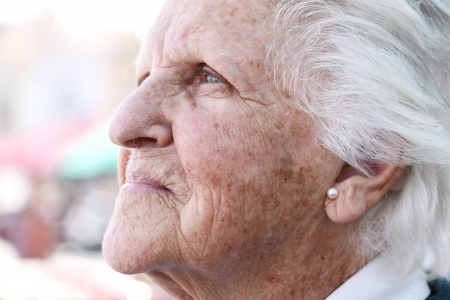 damages: profile portrait of a beaufitul octogenarian with white hair and wrinkled sun stained skin