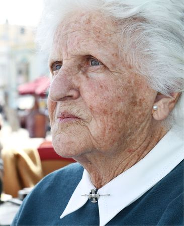 portrait of an old lady with wrinkles and sun stained skin and white hair Stock Photo