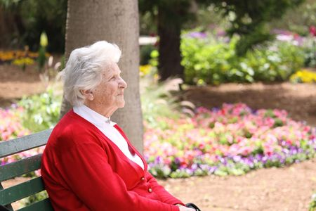 garden bench: an old caucasian octogenarian sitting on a park bench relaxing in the sun Stock Photo