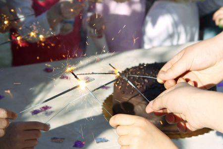 poco las manos ronda un sparklers de iluminación de pastel de cumpleaños para celebrar