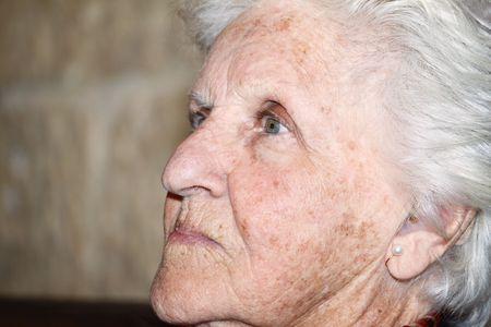 Ritratto di profilo di primo piano di una vecchia donna mostrando la invecchiamento della pelle con macchie di pigmentazione e sole