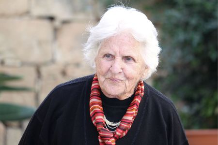 octogenarian: an old caucasian woman wearing a scarf and cardigan contemplating about something
