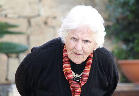 una anciana caucásicos plegado hacia abajo mostrando un back hunched