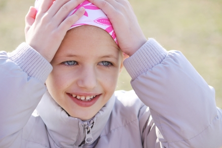 bald girl: child wearing head scarf due to hair los from chemotherapy treatment due to cancer Stock Photo