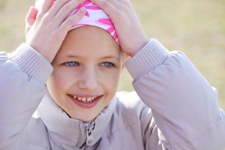 niño que llevaba el pañuelo de cabeza debido a los de pelo del tratamiento de quimioterapia debido a cáncer